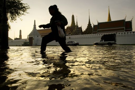 A woman walks through floodwaters in front of the Grand Palace near the Chao Praya river in Bangkok on October 27, 2011. Thai authorities urged residents in flood-prone areas of Bangkok to evacuate on October 26, warning them that the arrival of a massive deluge of water was imminent. TOPSHOTS     AFP PHOTO / Nicolas ASFOURI