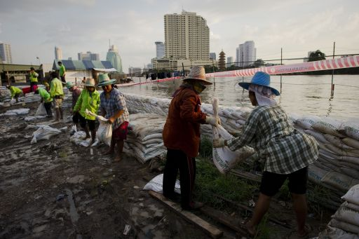 Workers reinforce a sand bag wall near China town next to the Chao Praya river in Bangkok on October 27, 2011. Thousands of Bangkok residents flocked to bus, rail and air terminals October 27 while heavy traffic snaked out of the sprawling Thai capital in an exodus from a mass of approaching floodwater. AFP PHOTO/ Nicolas ASFOURI
