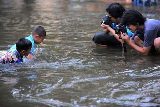 Thai photographers take pictures of children in floodwaters in Bangkok on October 27, 2011. Thousands of Bangkok residents flocked to bus, rail and air terminals on October 27,  while heavy traffic snaked out of the sprawling Thai capital in an exodus from a mass of approaching floodwater. AFP PHOTO/ TANG CHHIN SOTHY