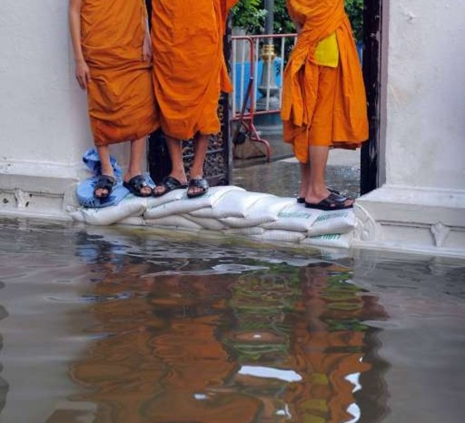 Thai Buddhist monks stand on sand bags in front of the gates of a pagoda surrounded by floodwaters in Bangkok on October 27, 2011. Thousands of Bangkok residents flocked to bus, rail and air terminals on October 27,  while heavy traffic snaked out of the sprawling Thai capital in an exodus from a mass of approaching floodwater. AFP PHOTO/ TANG CHHIN SOTHY