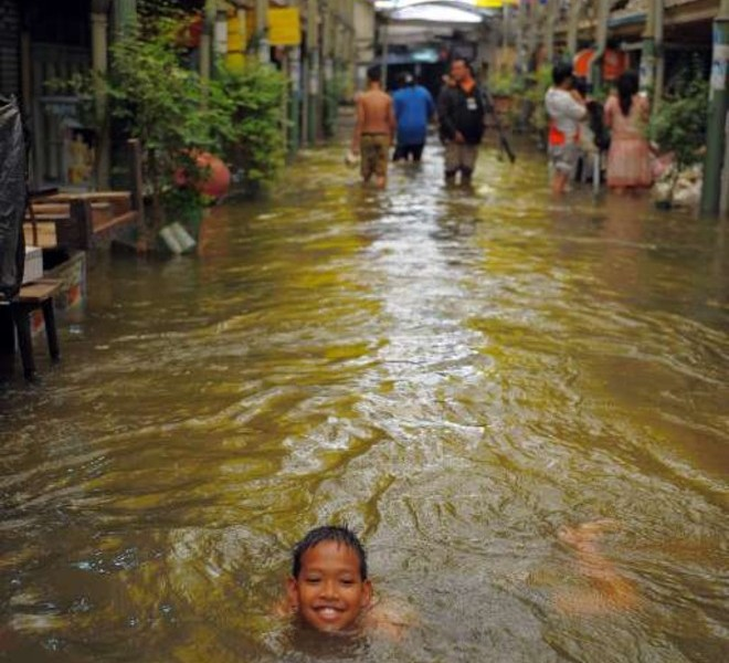A Thai boy swims in floodwaters in Bangkok on October 27, 2011. Thousands of Bangkok residents flocked to bus, rail and air terminals on October 27,  while heavy traffic snaked out of the sprawling Thai capital in an exodus from a mass of approaching floodwater. AFP PHOTO/ TANG CHHIN SOTHY