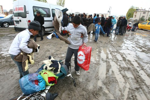 Two young boys look at clothes as homeless survivors queue to receive aid in Ercis on October 27, 2011, after a major earthquake of 7.2 magnitude hit eastern province of Van on October 23. Snow blanketed eastern Turkey, complicating rescue efforts and bringing more misery for the thousands left homeless by a devastating earthquake as the death toll surged past 530. Ninety-one hours after disaster struck in the eastern province of Van, rescuers pulled a 19-year-old from the rubble in the town of Ercis but the prospects of finding more people alive were fading fast. AFP PHOTO / ADEM ALTAN