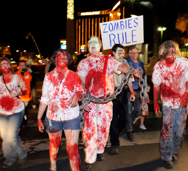 "LAS VEGAS, NV - OCTOBER 30:  Protesters affiliated with the Occupy Las Vegas movement (L-R) A.J. Ellis, Mercedes Haefer, James Kimmel, Christopher Rice, Dan Cooper and Daniel Reed, all of Nevada, participate in a ""zombie walk"" on the Las Vegas Strip October 30, 2011 in Las Vegas, Nevada. The demonstrators are protesting what they believe is greed and corruption among banking and business leaders in solidarity with other Occupy movements around the world.  (Photo by Ethan Miller/Getty Images)"