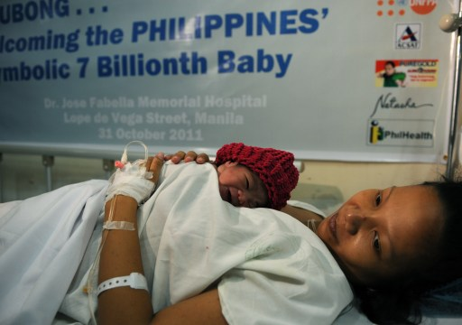 Danica Mae Camacho, the Philippine's symbolic 7 billionth baby is coddled by her mother Camille during a welcoming ceremony after she was given birth at a government-run maternity hospital in Manila early October 31, 2011. The Philippines welcomed its' symbolic seven billionth baby October 31 with a celebratory cheer at a packed government-run maternal hospital. Weighing 2.5 kilos, Danica May was delivered just shortly before midnight October 30 amid an explosion of flash bulbs from a media contingent that had waited for hours at Manila's Jose Fabella Memorial Hospital's delivery room. AFP PHOTO/TED ALJIBE