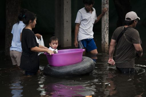 A toddler sits in a tub while pulled through floodwaters near the Chao Praya river in Bangkok on November 2, 2011. The death toll from Thailand's worst floods in decades surged above 400 as public anger simmered over the authorities' handling of the crisis. AFP PHOTO/ Nicolas ASFOURI
