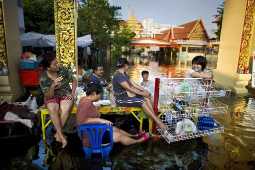 TOPSHOTS-Street food vendors and local residents gather over a table in floodwaters near the Chao Praya river in Bangkok on November 2, 2011. The death toll from Thailand's worst floods in decades surged above 400 as public anger simmered over the authorities' handling of the crisis. AFP PHOTO/ Nicolas ASFOURI