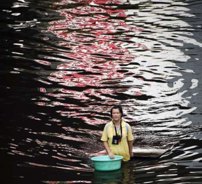 A local resident walks through floodwaters near the Chao Praya river in Bangkok on November 2, 2011. The death toll from Thailand's worst floods in decades surged above 400 as public anger simmered over the authorities' handling of the crisis. AFP PHOTO/ Nicolas ASFOURI