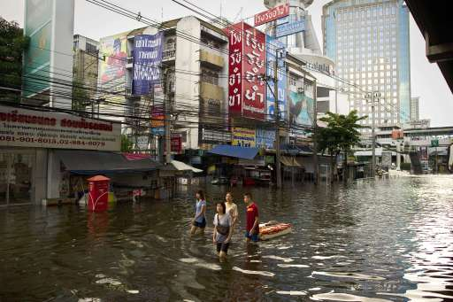 Local residents cross floodwaters near the Chao Praya river in Bangkok on November 2, 2011. The death toll from Thailand's worst floods in decades surged above 400 as public anger simmered over the authorities' handling of the crisis. AFP PHOTO/ Nicolas ASFOURI