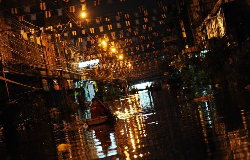 Local residents use boat through the floodwater near the Chao Praya river in Bangkok on November 2, 2011. Tensions were rising between Thai residents and authorities in flooded parts of Bangkok with hundreds protesting that their homes were being sacrificed in attempts to keep the city centre dry. AFP PHOTO/ SAEED KHAN