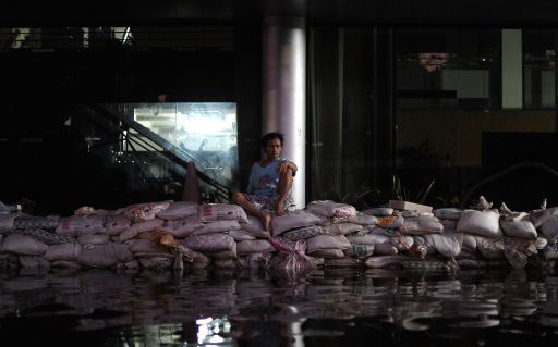 A Thai man sits on the sand bags in front of a government building in the flooded street near the Chao Praya river in Bangkok on November 2, 2011.The death toll from Thailand's worst floods in decades surged above 400 as public anger simmered over the authorities' handling of the crisis AFP PHOTO/ SAEED KHAN