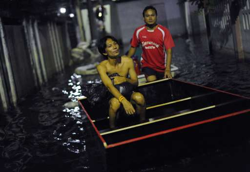 Local residents use a boat to cross through floodwaters near the Chao Praya river in Bangkok on November 2, 2011.  The death toll from Thailand's worst floods in decades surged above 400 as public anger simmered over the authorities' handling of the crisis.  AFP PHOTO/ SAEED KHAN