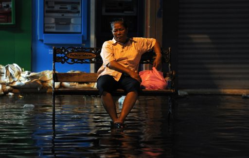 A Thai woman sits on a bench surrounded by floodwaters near the Chao Praya river in Bangkok on November 2, 2011. The death toll from Thailand's worst floods in decades surged above 400 as public anger simmered over the authorities' handling of the crisis. AFP PHOTO/ SAEED KHAN