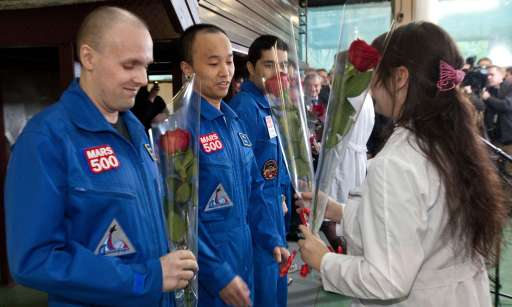 "A pool photo released by Moscow's Institute for Medical and Biological Problems on November 4, 2011, shows three of the six members of the Mars500 crew (L-R), Russian researcher Alexey Sitev,  Chinese Wang Yue and Italian-Colombian Diego Urbina, as they receive flowers after they emerged from the Mars500 isolation facility in Moscow. Six volunteers emerged today from isolation after spending almost one-and-a-half-years locked away from the world at a Russian research centre to test the effects on humans of a flight to Mars. The unprecedented experiment has simulated the duration and isolation of a return journey to the Red Planet, even including ""walks"" on a replica of the Martian surface and 20-minute time gaps in communication with outside.AFP-PHOTO/  MOSCOW'S INSTITUTE FOR MEDICAL AND BIOLOGICAL PROBLEMS/POOL/ OLEG VOLOSHIN"