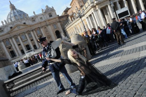 A policemen grabs the placard held by an activist of the Ukrainian women movement Femen in front of St Peter's basilica after holding a placard asking for 'Freedom for women' following Pope Benedict XVI's Angelus prayer on November 6, 2011 at St Peter's square at The Vatican.  AFP PHOTO / ANDREAS SOLARO