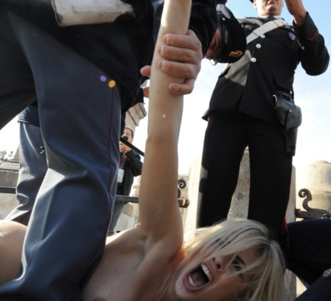 An activist of the Ukrainian women movement Femen is arrested by policemen in front of St Peter's basilica after holding a placard asking for 'Freedom for women' following Pope Benedict XVI's Angelus prayer on November 6, 2011 at St Peter's square at The Vatican.  AFP PHOTO / ANDREAS SOLARO
