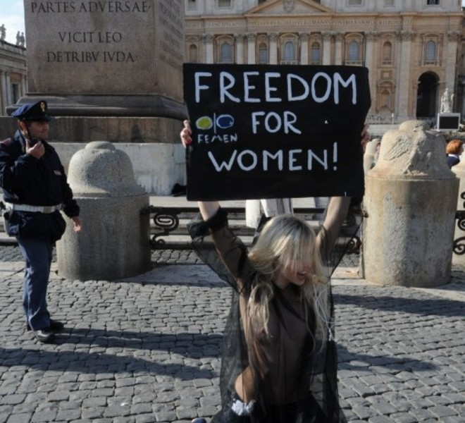 A policeman gets close to an activist of the Ukrainian women movement Femen holding a placard asking for 'Freedom for women' at St Peter's square after Pope Benedict XVI lead the Angelus prayer on November 6, 2011 at The Vatican.  AFP PHOTO / ANDREAS SOLARO