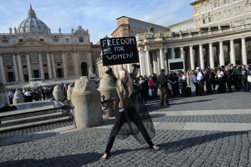 An activist of the Ukrainian women movement Femen holds a placard asking for 'Freedom for women' at St Peter's square following Pope Benedict XVI's Angelus prayer on November 6, 2011 at The Vatican.  AFP PHOTO / ANDREAS SOLARO