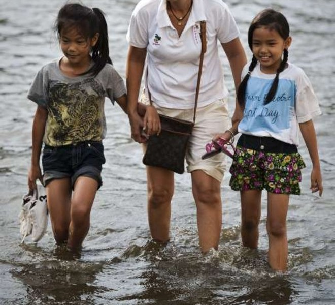 A woman holds the hands of two girls as they walk through floodwaters in the Lat Phrao shopping and business district in Bangkok on November 8, 2011. Thailand's prime minister said she would miss an Asia-Pacific summit in Hawaii this weekend, postponing her debut on the world stage to deal with the kingdom's worst floods in half a century. AFP PHOTO/ Nicolas ASFOURI