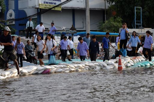 Factory workers walk on a sandbag barrier, placed in an attempt to prevent floodwaters from entering the premises, in the northeastern Bangchan industrial district of Bangkok on November 8, 2011. More than 1.7 million people have been told to evacuate 12 out of Bangkok's 50 districts, while partial evacuations have been ordered in five others. AFP PHOTO/ SAEED KHAN