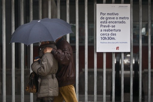 "A couple walks past a sign, reading: ""Due to a strike the metro is closed. Planned reopening at 10h30"", at the Cais do Sodre railway station in the center of Lisbon on November 8 , 2011 during a partial strike of public transports. Public transport services were severely disrupted across Portugal on November 8 as workers went on strike over a government program of tough austerity measures to help Portugal survive the euro crisis. AFP PHOTO/PATRICIA DE MELO MOREIRA"