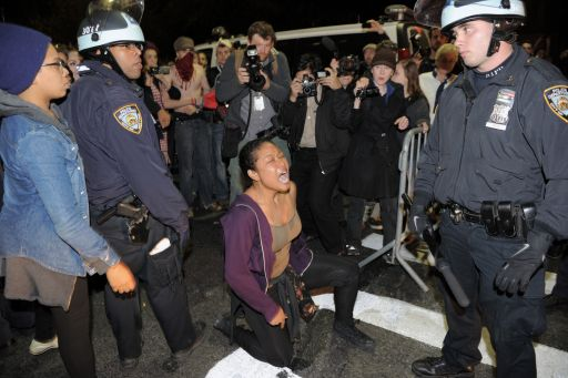A woman yells at New York Police Department officers as New York City officials clear the 'Occupy Wall Street' protest from Zuccotti Park in the early morning hours of November 15, 2011 in New York. The surprise crackdown at the birthplace of the movement, launched after similar evictions in other cities, signaled a tougher line by US authorities towards the two-month old protests against Wall Street and Washington elites.    AFP PHOTO/Stan HONDA