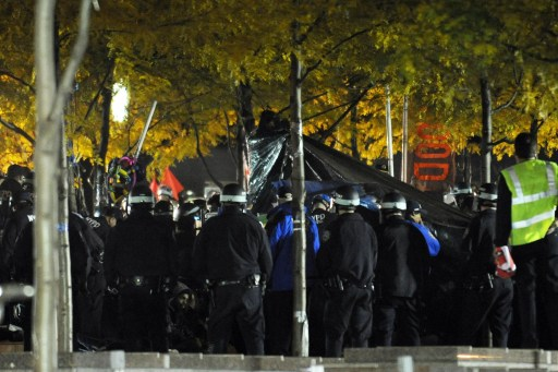 New York Police Department officers surround a central tent as they clear the 'Occupy Wall Street' protest from Zuccotti Park in the early morning hours of November 15, 2011 in New York. The surprise crackdown at the birthplace of the movement, launched after similar evictions in other cities, signaled a tougher line by US authorities towards the two-month old protests against Wall Street and Washington elites.     AFP PHOTO/Stan HONDA