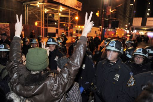 A man flashes peace signs at New York Police Department officers a few blocks from Zuccotti Park they clear the 'Occupy Wall Street' protest from the park in the early morning hours of November 15, 2011 in New York. The surprise crackdown at the birthplace of the movement, launched after similar evictions in other cities, signaled a tougher line by US authorities towards the two-month old protests against Wall Street and Washington elites.   AFP PHOTO/Stan HONDA