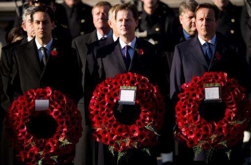 Britain's Prime Minister David Cameron (R), Deputy Prime Minister Nick Clegg (C) and Leader of the Labour Party Ed Miliband (L) hold wreaths during the Remembrance Sunday service in Whitehall, England on November 13, 2011. Queen Elizabeth II led Britain in honouring its war dead as the country fell silent on its national remembrance day. In bright autumn sunshine, the queen laid the first wreath at the Cenotaph memorial in London to commemorate members of the armed forces who have died fighting in all conflicts since World War I.  AFP PHOTO/Leon Neal