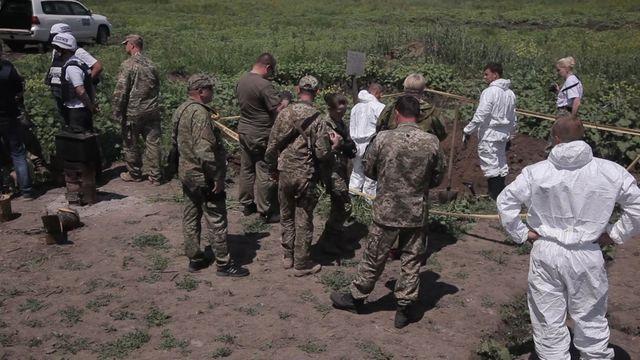 Взахоронении наДонбассе нашли тела сроссийскими шевронами