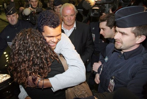 French tennis player Jo-Wilfried Tsonga (L), flanked by French Tennis Federation President Christian Bimes (C, background) hugs a friend  as he arrives 29 january 2008 at Paris Roissy airport, two days after his final in the Australian Open against Novak Djokovic of Serbia, in Melbourne. The unseeded Frenchman went down in four sets but his ranking will climb to 18 from 38 courtesy of his giantkilling run in Melbourne where he claimed four seeded scalps.     AFP PHOTO PATRICK KOVARIK