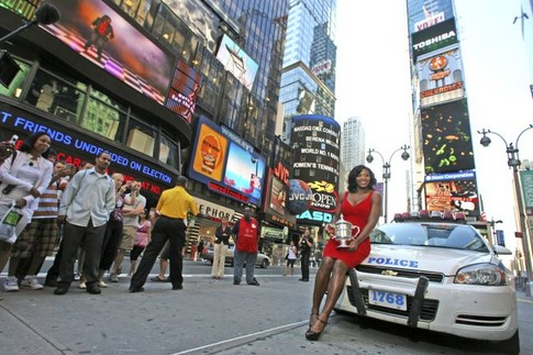 Serena Williams, of the United States, holds up her U.S. Open championship trophy while posing for photographers in New York's Times Square, Monday, Sept. 8, 2008 in New York. Williams defeated Jelena Jankovic, of Serbia, to win the women's finals championship match at the U.S. Open tennis tournament in New York, Sunday, Sept. 7, 2008.   (AP Photo/Mary Altaffer)