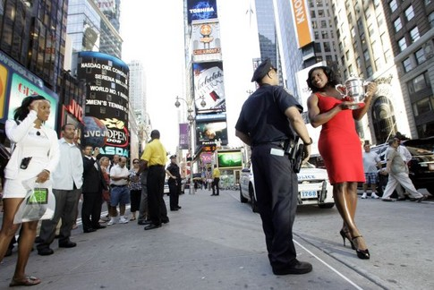 Serena Williams, right, of the United States, holding her U.S. Open championship trophy, chats with police officer Chris Vital while posing for photographers in New York's Times Square, Monday, Sept. 8, 2008. Williams defeated Jelena Jankovic, of Serbia, to win the women's finals championship match at the U.S. Open tennis tournament in New York, Sunday, Sept. 7, 2008.  (AP Photo/Mary Altaffer)